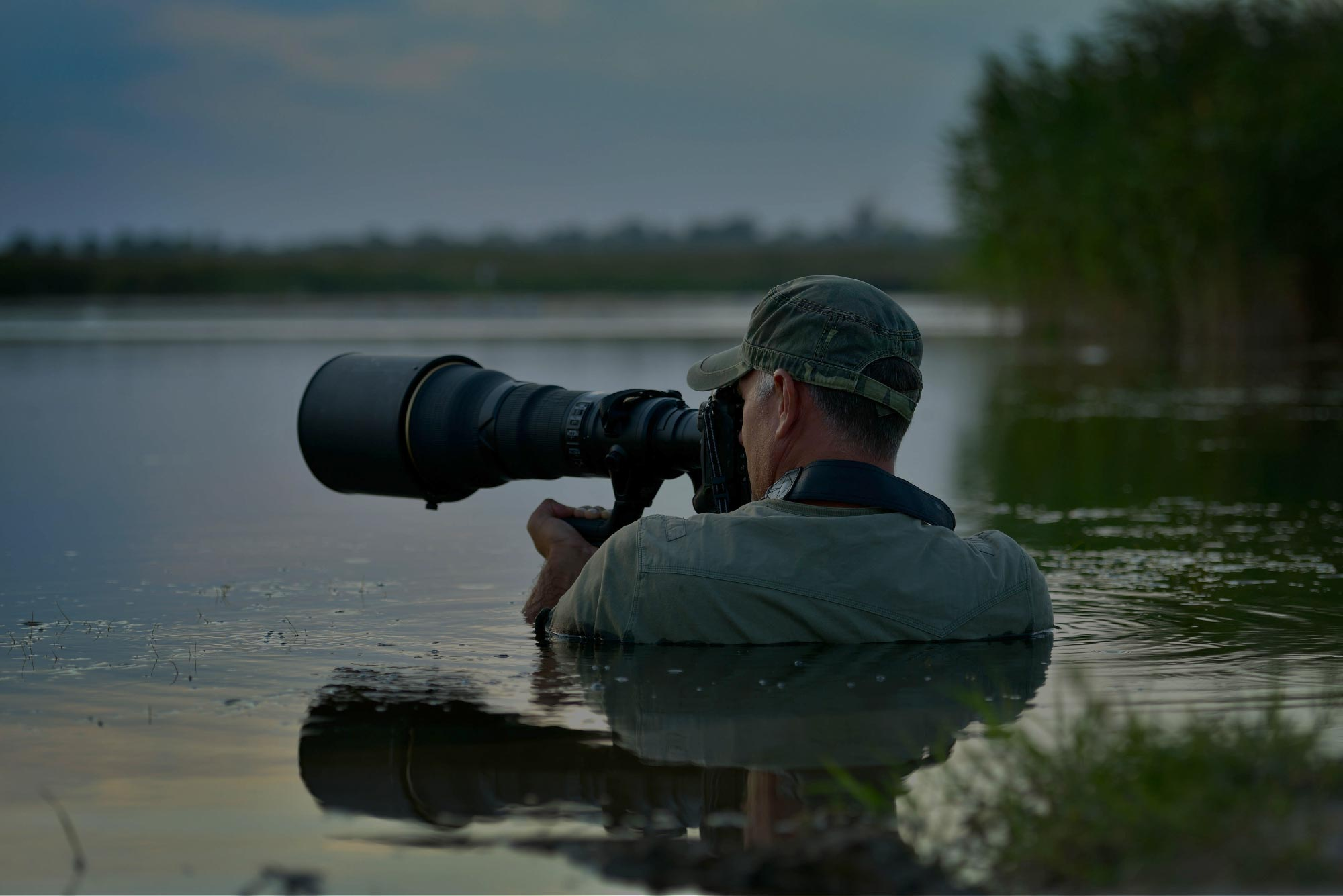 man photographing in water with large camera lens