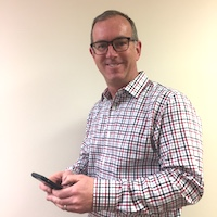 chris stands with his phone at Quiq Headquarters working on customer service messaging solutions