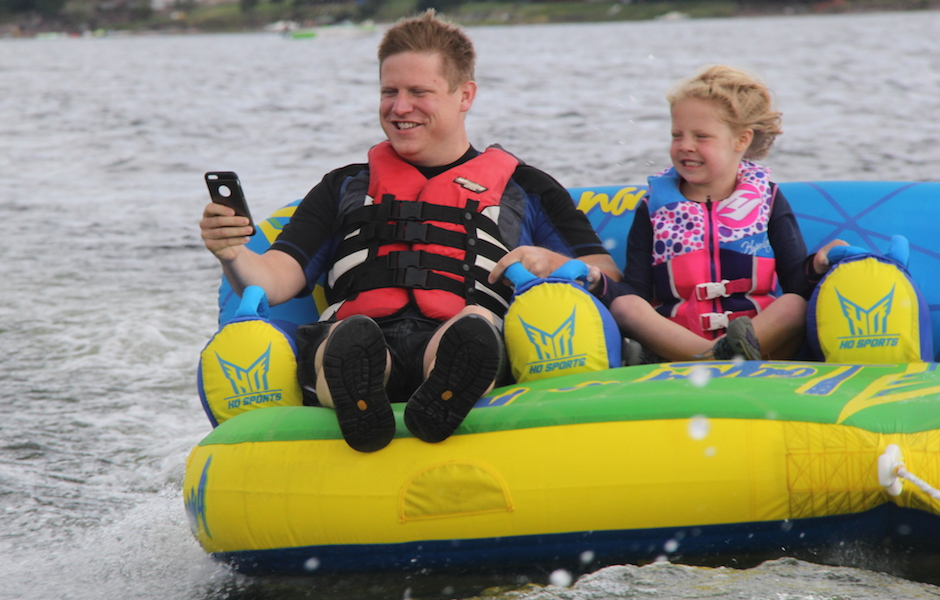 matt and emma riding on water inflatable while testing facebook messenger customer service software