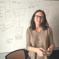 susan messages customer service while standing in front of whiteboard depicting customer experience workflow
