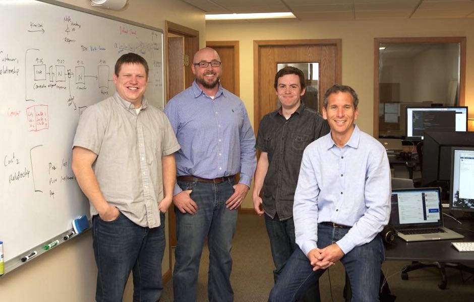 Quiq team smiles next to whiteboard showing love of business messaging software