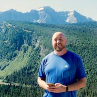 bill stands outside at glacier national park using facebook messenger for customer service
