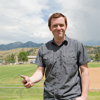 nate messaging at baseball field with mountains in background