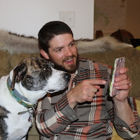 philip and dog on mobile device working on customer service messaging software