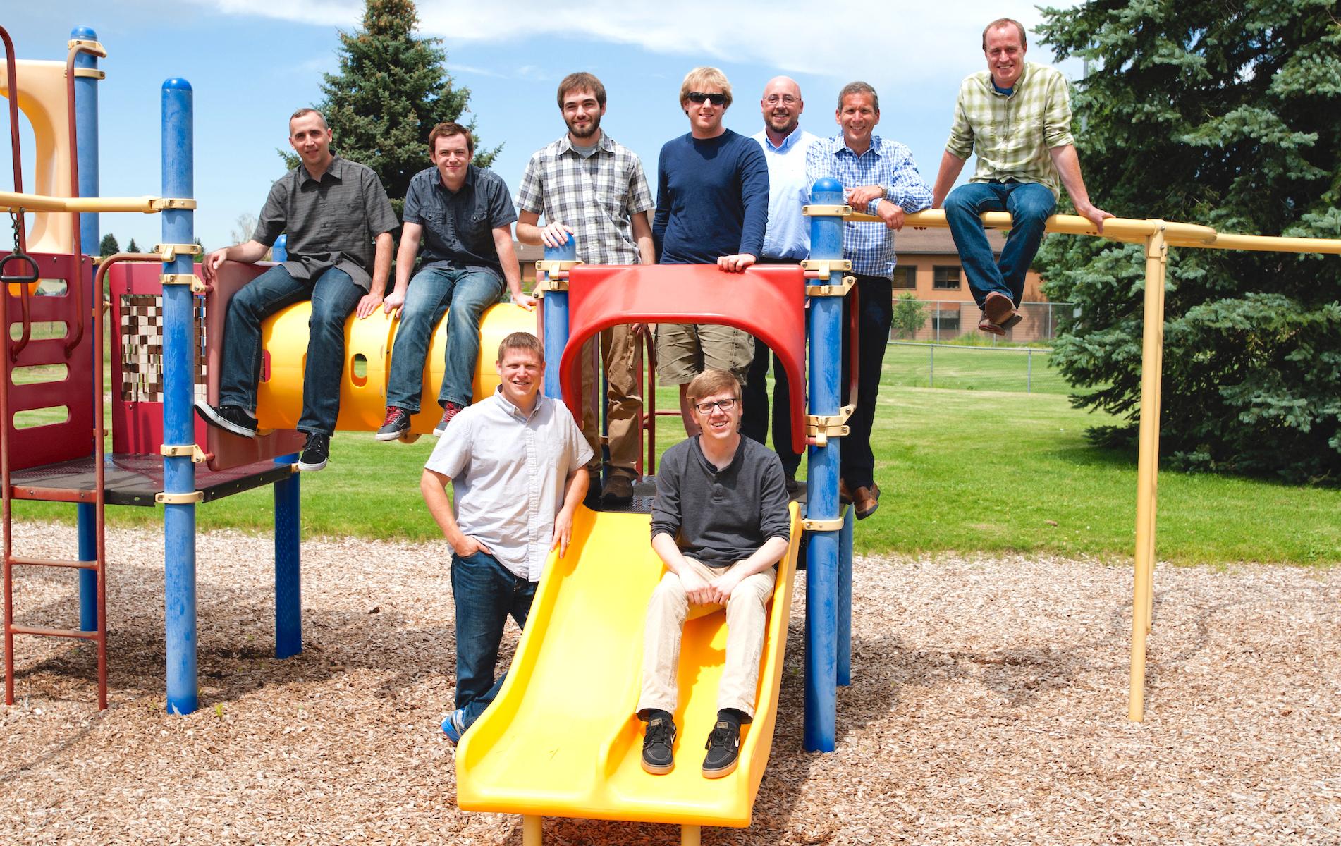quiq customer messaging staff poses on playground equipment
