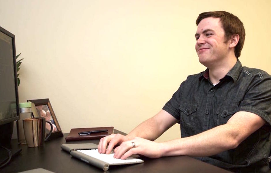 nate smiling and laughing in front of mobile messaging software on desktop