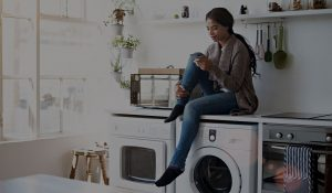 Quiq Customer Messaging platform used by a happy woman sitting on washing machine