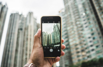 Man holding cell phone up and taking a low angle picture of a tall city skyline
