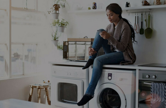 Woman sitting on her washing machine while glancing at her phone