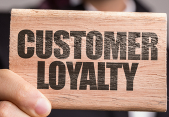 "person holding a small piece of wood with the words ""customer loyalty"" printed on it"