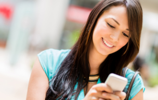 Woman with brown hair and blue shirt smiles down at her phone