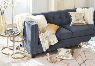 Modern navy blue couch with white and gold pillows