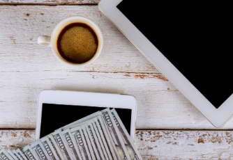 an iPhone and an iPad on a table with a cup of coffee and hundred dollar bills