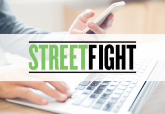 person typing on laptop and holding a phone, Streetfight graphic over top