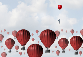 Businessman holding a red balloon and floating in the sky above hot air balloons