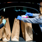People wearing gloves delivering curbside groceries into a car trunk